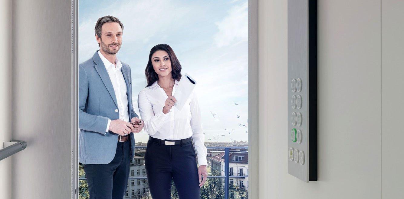 мъж и жена пред асансьорна кабина на асансьор ThyssenKrupp Synergy 100