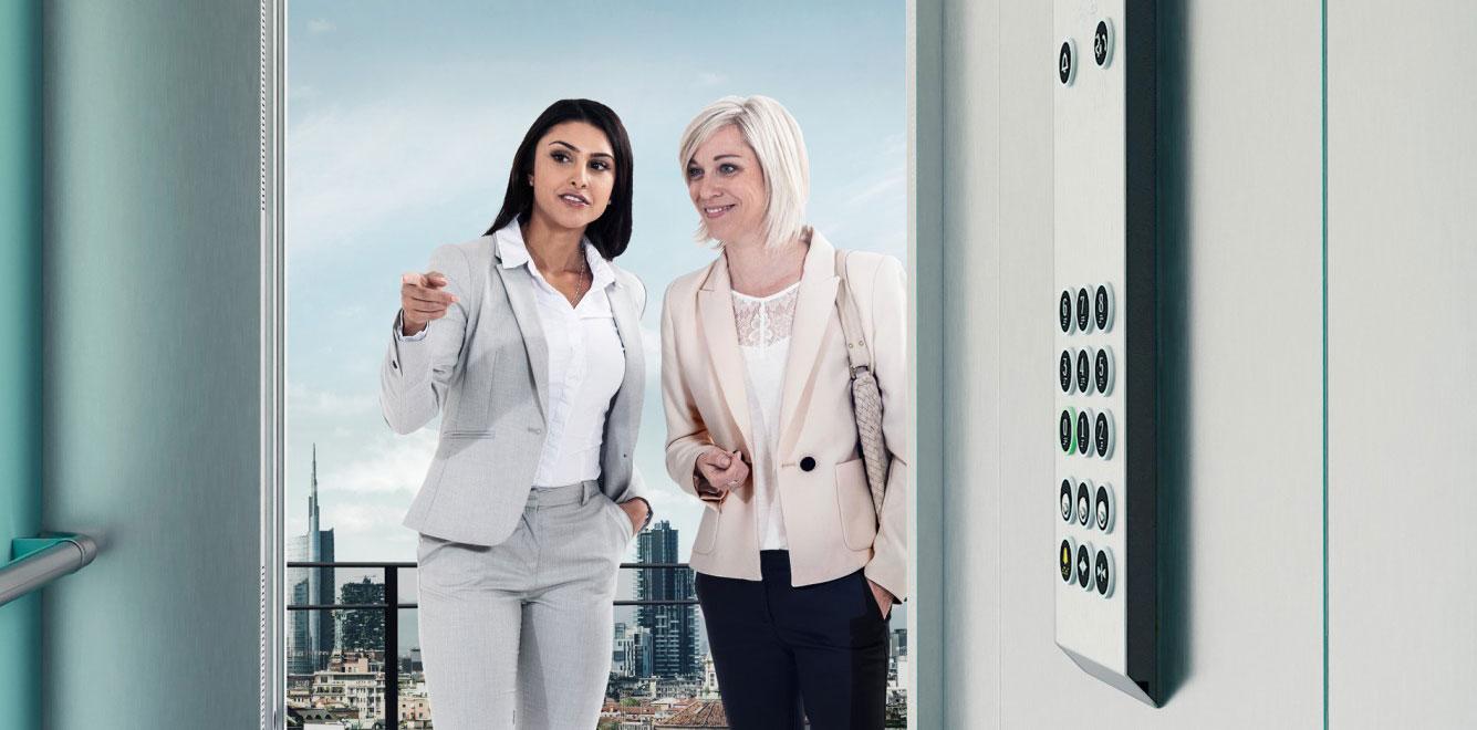 асансьор ThyssenКrupp Synergy 300 - корица с две жени в асансьорна кабина
