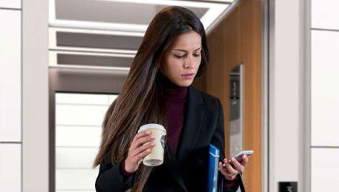 млада жена излиза от асансьор ThyssenKrupp Synergy 300