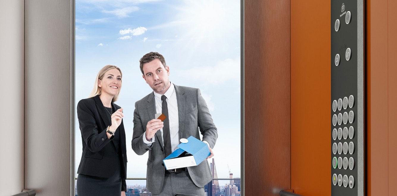 мъж и жена пред асансьорна кабина на асансьор ThyssenKrupp Synergy 200