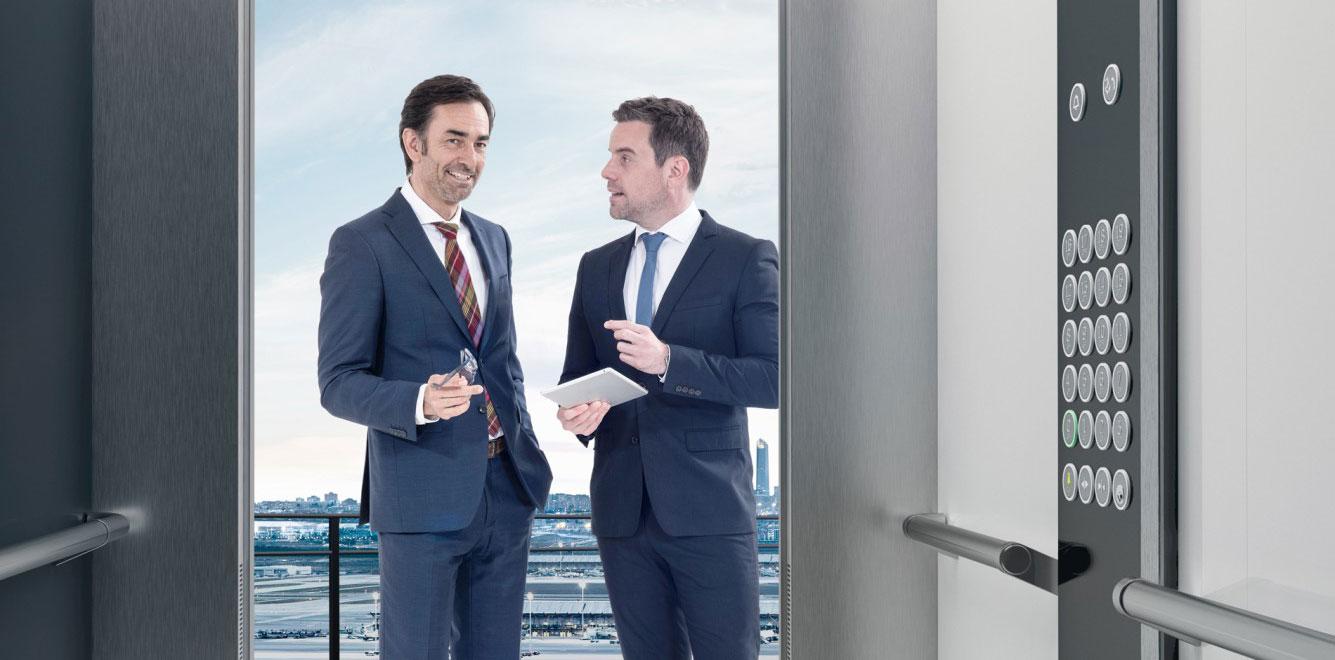двама мъже пред асансьорна кабина на асансьор ThyssenKrupp Synergy 300